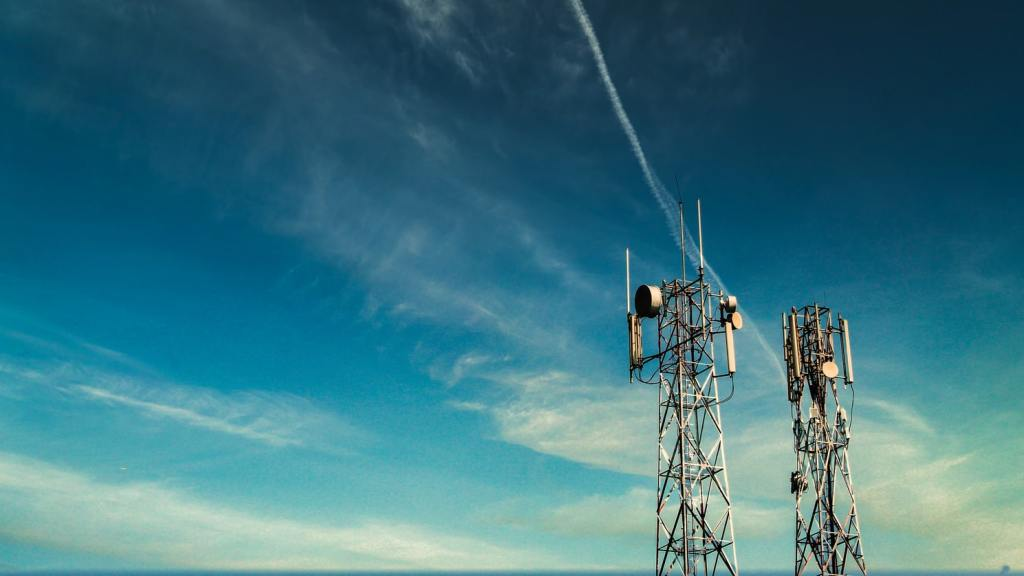 Two cell phone towers in front of a blue sky